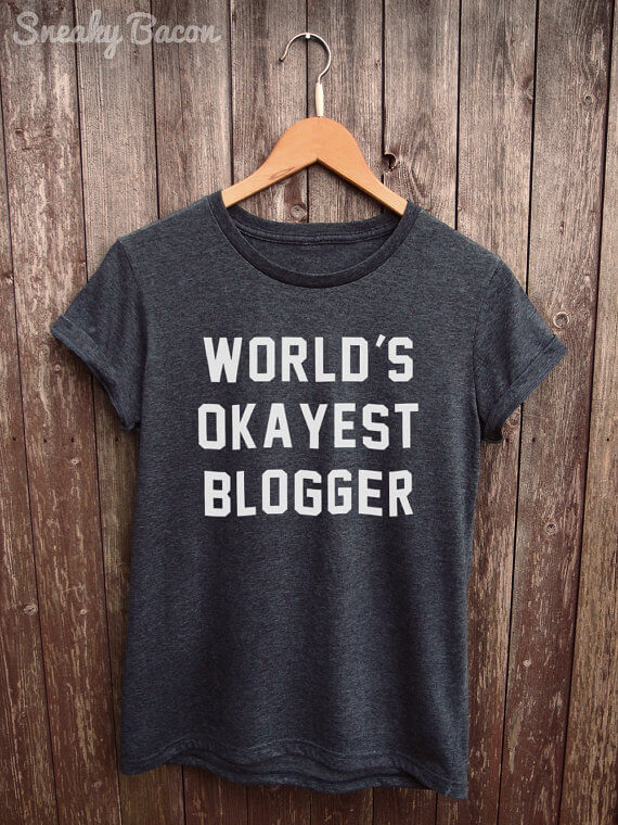 """Know a blogger with a great sense of humor? (Or maybe that's you?!) Grab this """"world's okayist blogger"""" tee! See more in this Fun Gift Guide for Entrepreneurs at www.CreatingBeautifully.com!"""